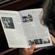 A Woman Reads From the Commemorative Program